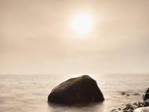 I massi alla riva dell'isola attaccano su dal mare liscio La costa pietrosa sfida alle onde Immagini Stock