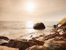 I massi alla riva dell'isola attaccano su dal mare liscio La costa pietrosa sfida alle onde Fotografie Stock