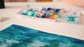 I materiali illustrativi dell'acquerello della pittura dell'artista passano la spazzola stock footage