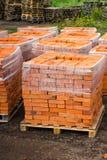I mattoni dell'argilla rossa sono impilati sui pallet di legno Produzione dei mattoni da argilla immagini stock