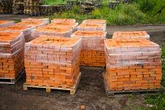 I mattoni dell'argilla rossa sono impilati sui pallet di legno Produzione dei mattoni da argilla fotografie stock libere da diritti