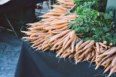 I mazzi di carote sono accatastati su una Tabella ad una stalla del venditore in un mercato fotografia stock