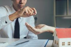 I mediatori di casa del rappresentante forniscono chiave ai nuovi proprietari di abitazione in ufficio fotografia stock