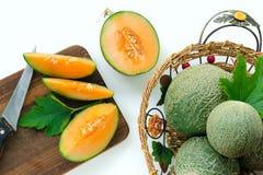I meloni maturi incidono i pezzi su un bordo di legno Interi meloni nel canestro Priorità bassa bianca immagini stock libere da diritti