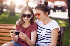 I migliori amici abbracciano mentre sieda sul banco nel parco dell'estate, brevi video dell'orologio sul telefono cellulare, conn Fotografia Stock Libera da Diritti