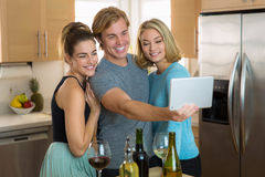 I migliori amici si avvicinano per un selfie su un dispositivo astuto della compressa nella cucina ad una festa Fotografia Stock