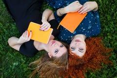I migliori amici sono insieme studentesse su prato inglese Fotografia Stock Libera da Diritti