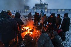 I migranti sono heated sopra un fuoco nella neve e nel freddo Fotografie Stock