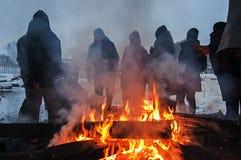 I migranti sono heated sopra un fuoco nella neve e nel freddo Fotografia Stock