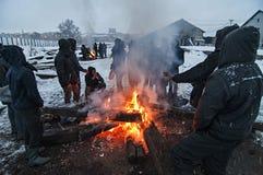 I migranti sono heated sopra un fuoco nella neve e nel freddo Immagini Stock Libere da Diritti