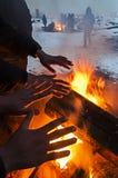 I migranti sono heated sopra un fuoco nella neve e nel freddo Immagine Stock