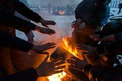 I migranti sono heated sopra un fuoco nella neve e nel freddo Immagini Stock