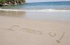 I miss u written in sand in tropical beach scene. I miss u written in sand on tropical beach near blue water Royalty Free Stock Image