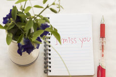 I miss you i love you message card write on notebook with flowers. I miss you message card write on notebook with flowers in flowerpot Stock Photo