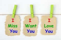 I Miss You, I Want You, I Love You. Written on old torn paper with clip hanging royalty free stock photos