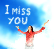 I miss you message in sky. Closeup of pining young woman with outstretched arms looking at message, I miss you, written with clouds in sky Stock Illustration