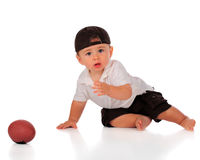 I Missed It. An adorable baby boy looking forlorn as he heads toward his football. Isolated on white royalty free stock photos