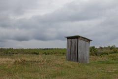 I mitt av ängen står en lantlig offentlig toalett som göras av träplankor royaltyfri fotografi