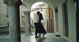 I mitt av den fantastiska arkitektoniska gatan i Italien ett ungt par som möter sig romantiskt krama och att starta till stock video