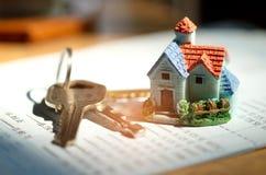 I modelli e la chiave domestici della casa hanno messo sopra il bookbank, soldi di concetto per comprare la a Fotografie Stock Libere da Diritti