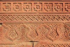 I modelli floreali e geometrici sono stati scolpiti su una parete a Qutb minar a Nuova Delhi (India) Immagine Stock