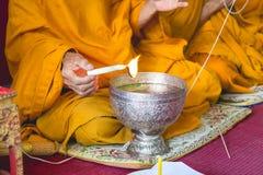 I monaci di buddismo sono pregano e formalizzano l'acqua santa o l'acqua benedetta Fotografie Stock