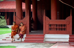 I monaci si siedono per resto e li aspettano amici al palazzo di Mandalay fotografia stock libera da diritti