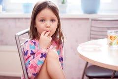 I morgonen har flickan frukosten Arkivfoto