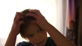 I morgonen kammar en ung man hans hår framme av fönstret Strålarna för sol` s passerar till och med exponeringsglaset stock video