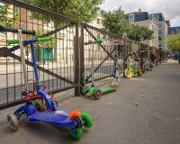 I motorini dei bambini sono bloccati al cortile della scuola recintano Parigi Immagine Stock Libera da Diritti