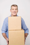I am moving to a new place. Middle aged man carrying stack of carton boxes vector illustration