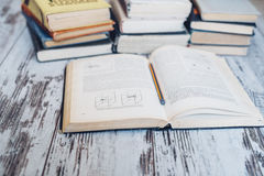 I mucchi dei libri con un libro aprono e disegnano a matita lzing alle sue pagine Fotografia Stock Libera da Diritti