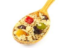 I muesli o l'avena del cereale si sfaldano con frutta secca sul cucchiaio di legno, isolato Fotografia Stock