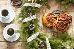 I muffin del cioccolato della lumaca sono servito con caffè sui precedenti di una corona dei rami e dei coni dell'abete Stile rus fotografia stock