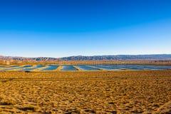 I mulini a vento coltivano e serbatoi di acqua lungo una strada principale in deserto del Mojave Fotografia Stock