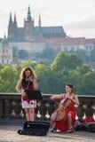 I musicisti della via eseguono con Praga Castel su fondo Immagine Stock Libera da Diritti