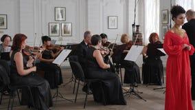 I musicisti giocano sui violini sotto la direzione del conduttore per un cantante della donna in vestito da sera rosso stock footage