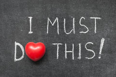 I must do this. Exclamation handwritten on blackboard with heart symbol instead of O Stock Photography