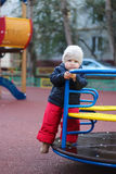 I am myself. Cute baby trying to ride on a merry-go-round Stock Image