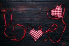 I nastri hanno modellato come amore di parola su fondo e su handm di legno scuri Immagini Stock
