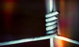 I nastri metallici nel collegamento stretto su buio hanno colorato il fondo Immagine Stock Libera da Diritti