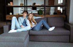 I naturlig storlek stående av attraktiva moderiktiga par som sitter i modern öppet utrymmelägenhet royaltyfria bilder