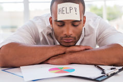 I need help. Frustrated young African man in formalwear with adhesive note on his forehead leaning his head at the table Royalty Free Stock Photos