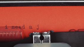 I need a job - Typed on a old vintage typewriter. Printed on red paper. The red paper is inserted into the typewriter stock video footage