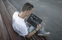 I need job. Young man writing I need job in spanish on a blackboard stock photo