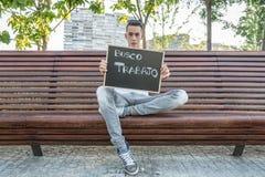 I need job. Young man writing I need job in spanish on a blackboard Royalty Free Stock Photo