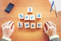 I need love. Businessman made text from wooden cubes royalty free stock image