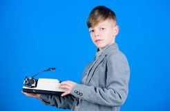 I need modern gadget instead this retro. Outdated gadget. Retro and vintage. Yard sale. Retrospective study. Boy hold. Retro typewriter on blue background. What stock photos