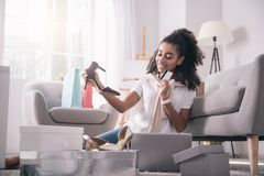 Delighted positive woman buying new pair of shoes. I need more. Delighted positive woman buying a new pair of shoes while being shopping addicted Stock Photo