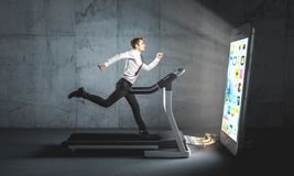 I need my smartphone. Businessman runs on a treadmill to feed a big smartphone he can`t do without. Concept of attachment to technology and dependence royalty free stock image
